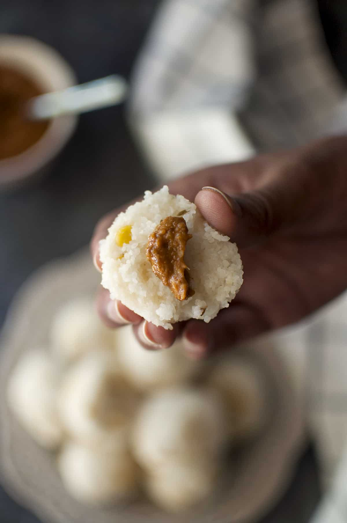 Hand holding half kudumu topped with ginger chutney