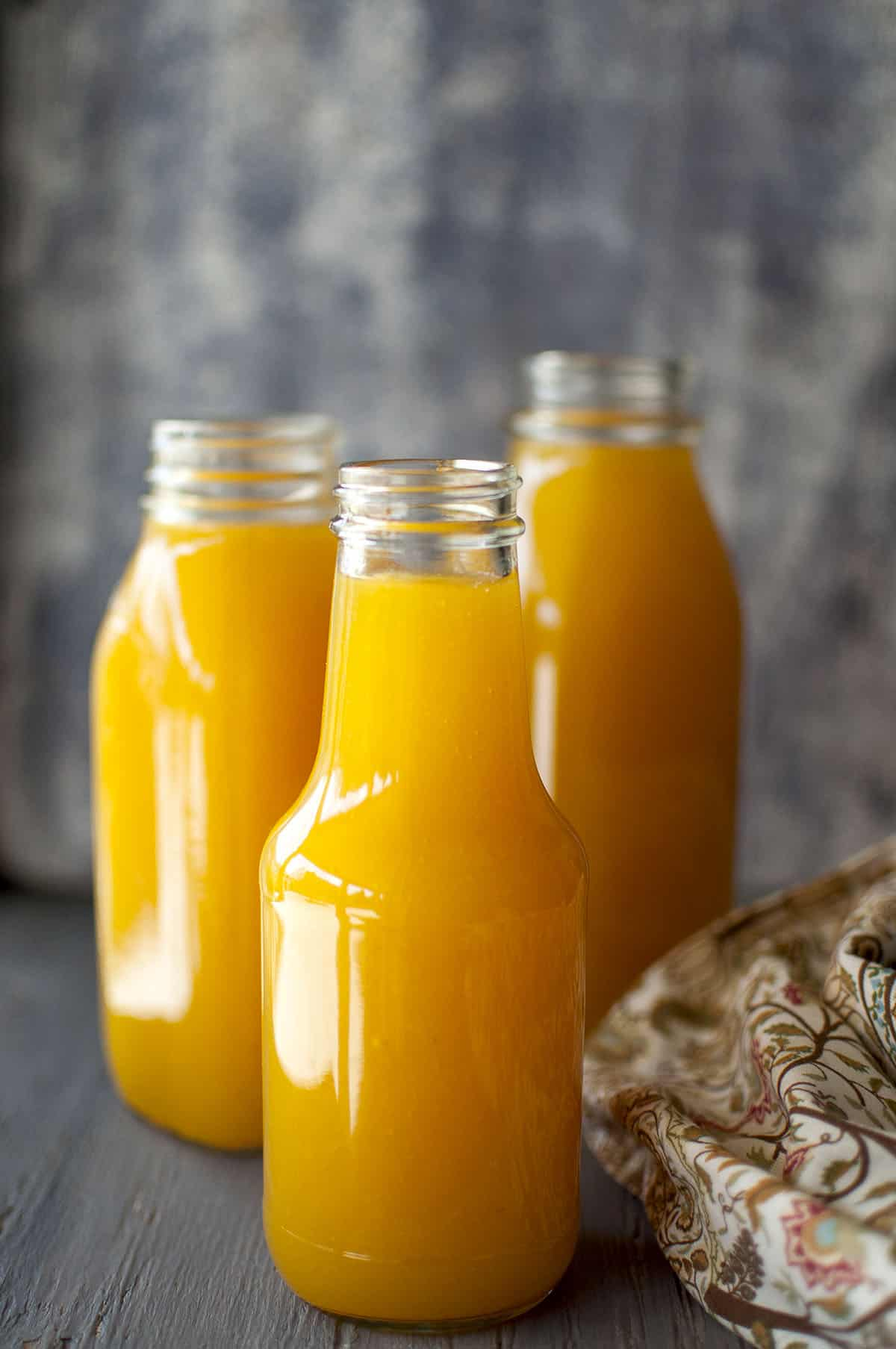 3 glass bottles with mango juice concentrate