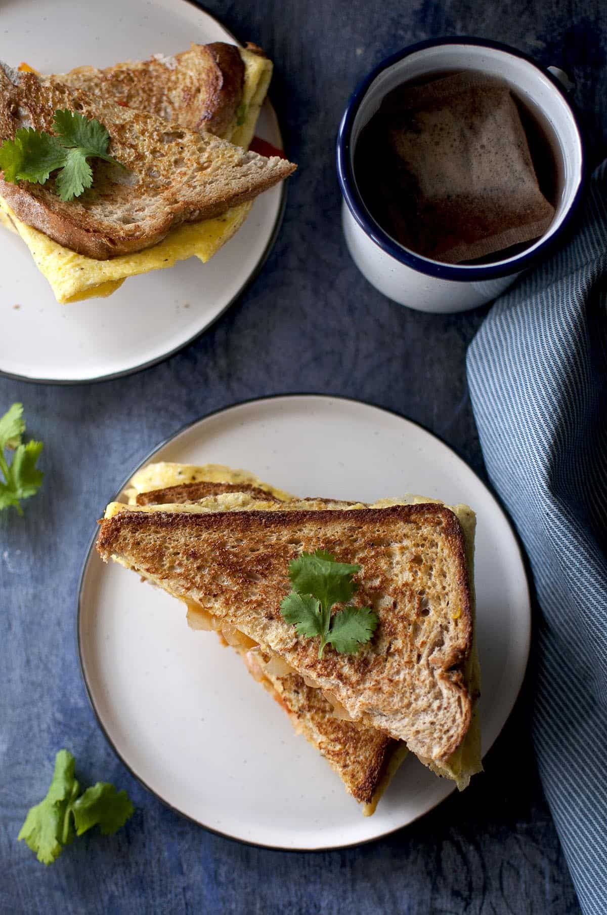 Top view of egg toast sandwich on a white plate with a enamel mug with tea in the background