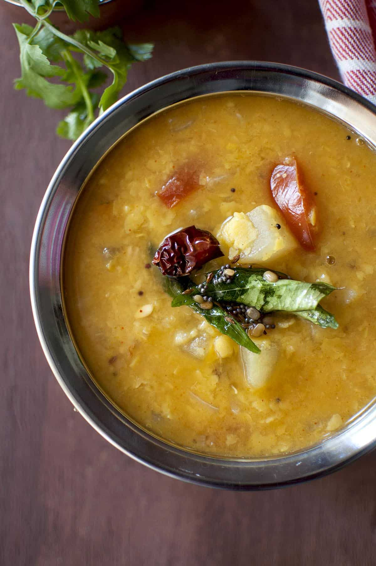 steel bowl with yellow cucumber dal