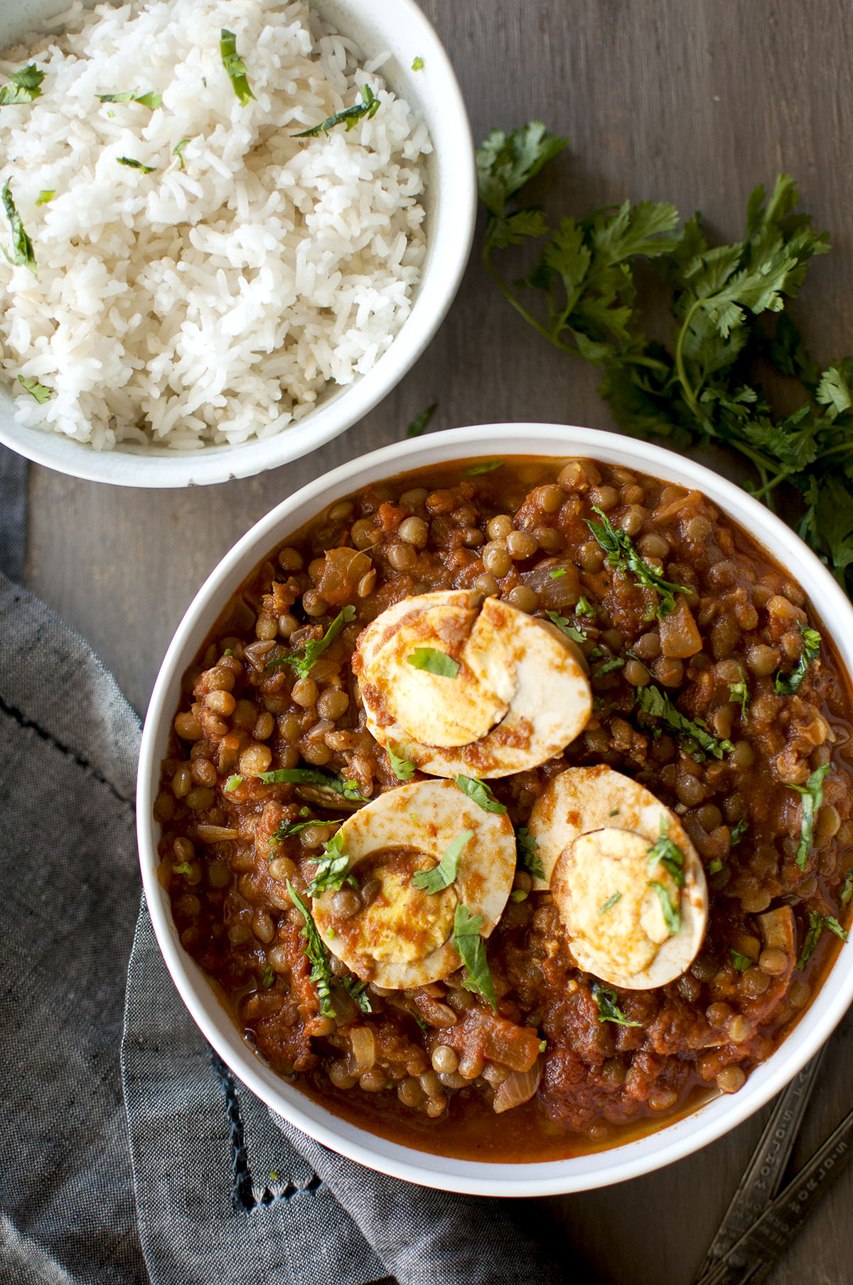 White bowl with lentils curry topped with egg halves served with a bowl of white rice