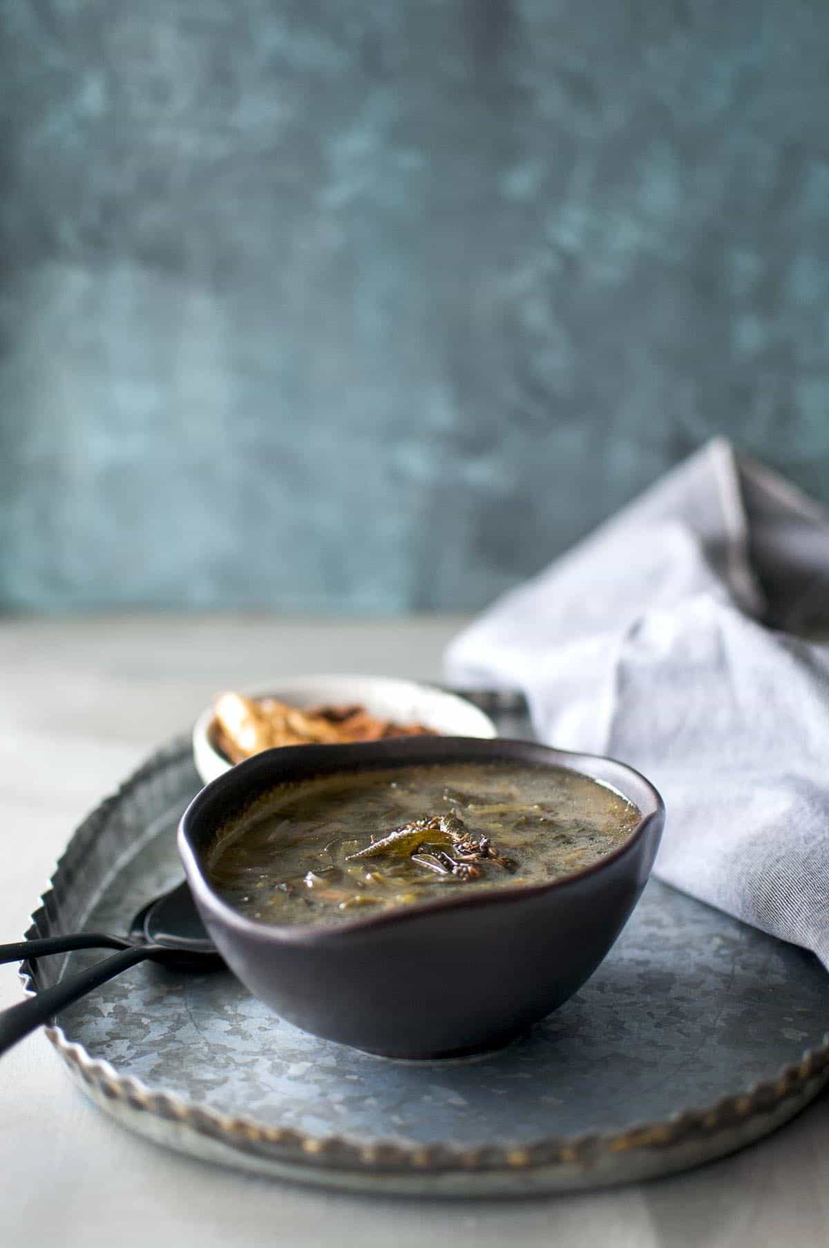 pewter tray with black bowl with spinach soup