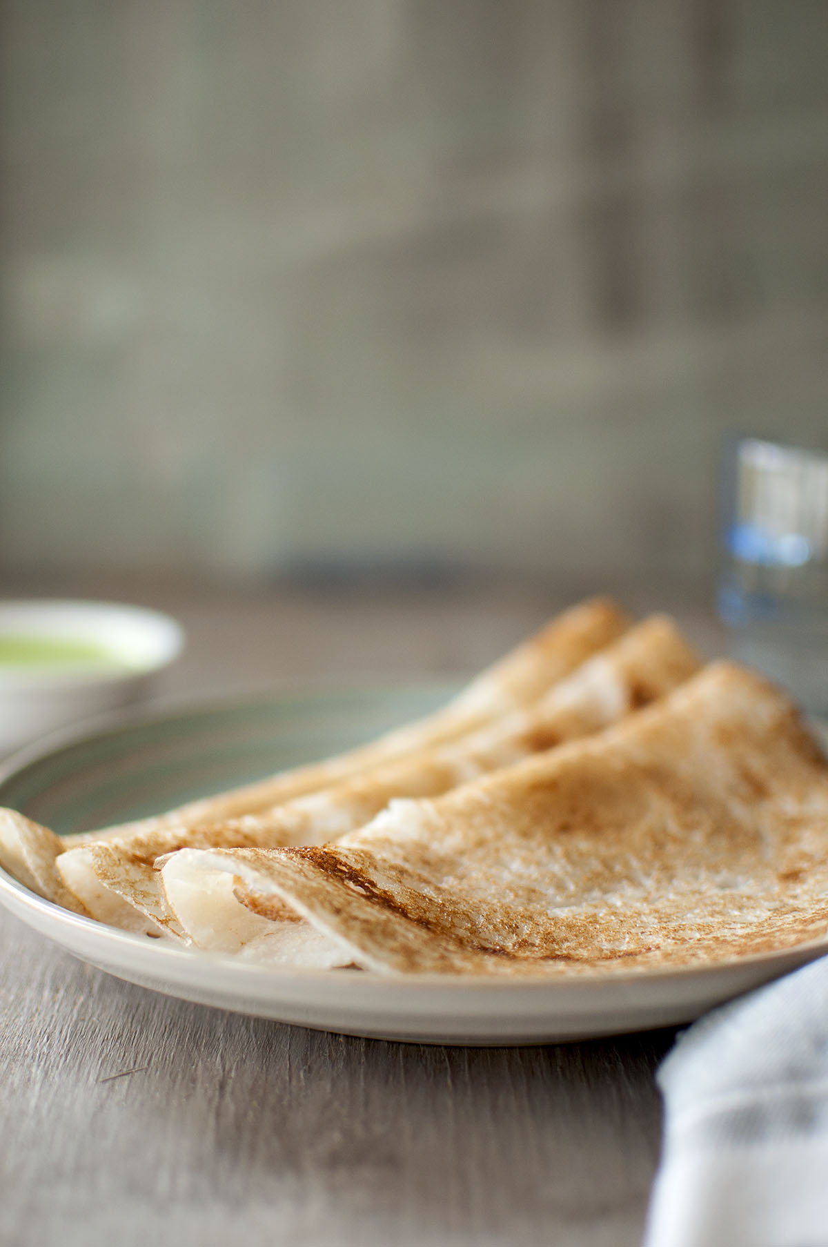 Blue plate with Indian crepes, poha dosa, with chutney