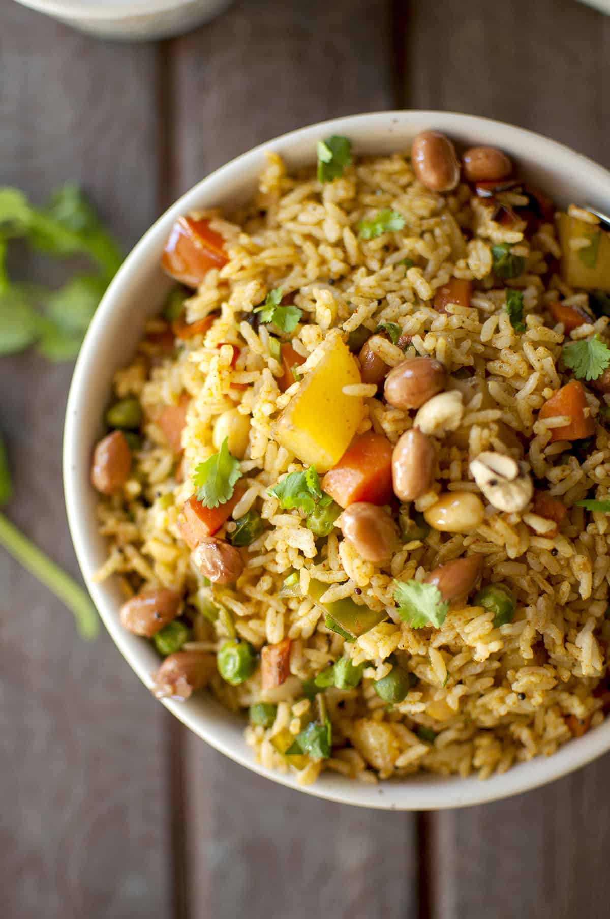 White bowl with colorful vegetable rice topped with peanuts and cashews