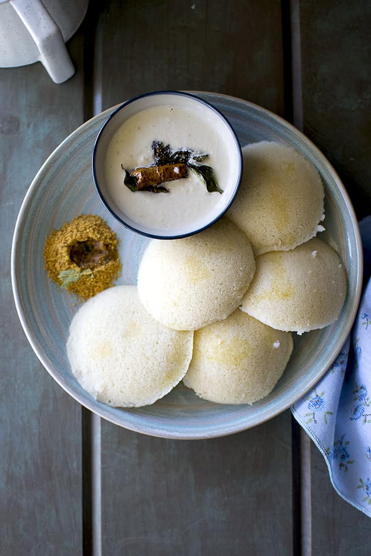 Blue plate with 5 idli with podi and coconut chutney