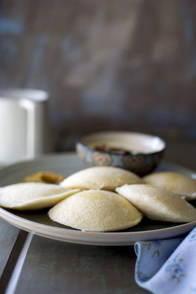 Grey plate with steamed idli and coconut chutney