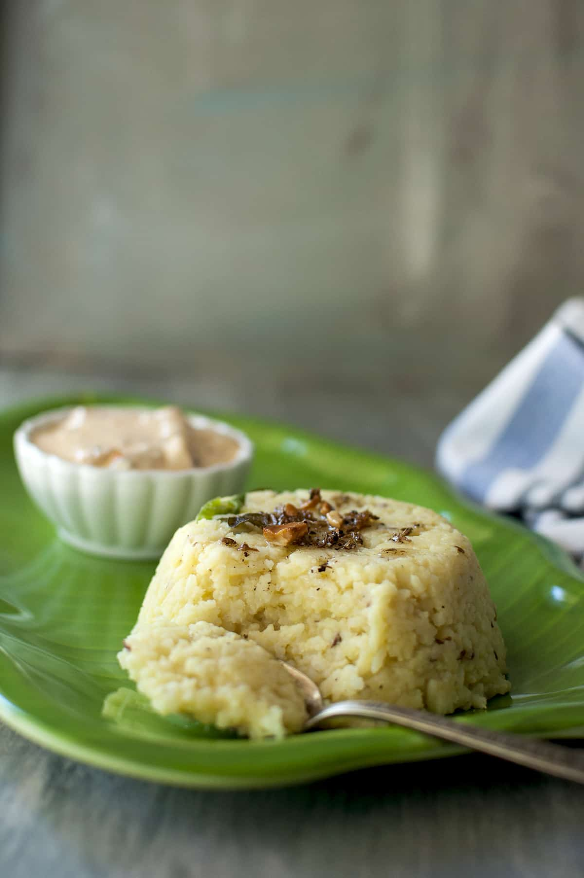 green plate with a spoon of scooped up pongal