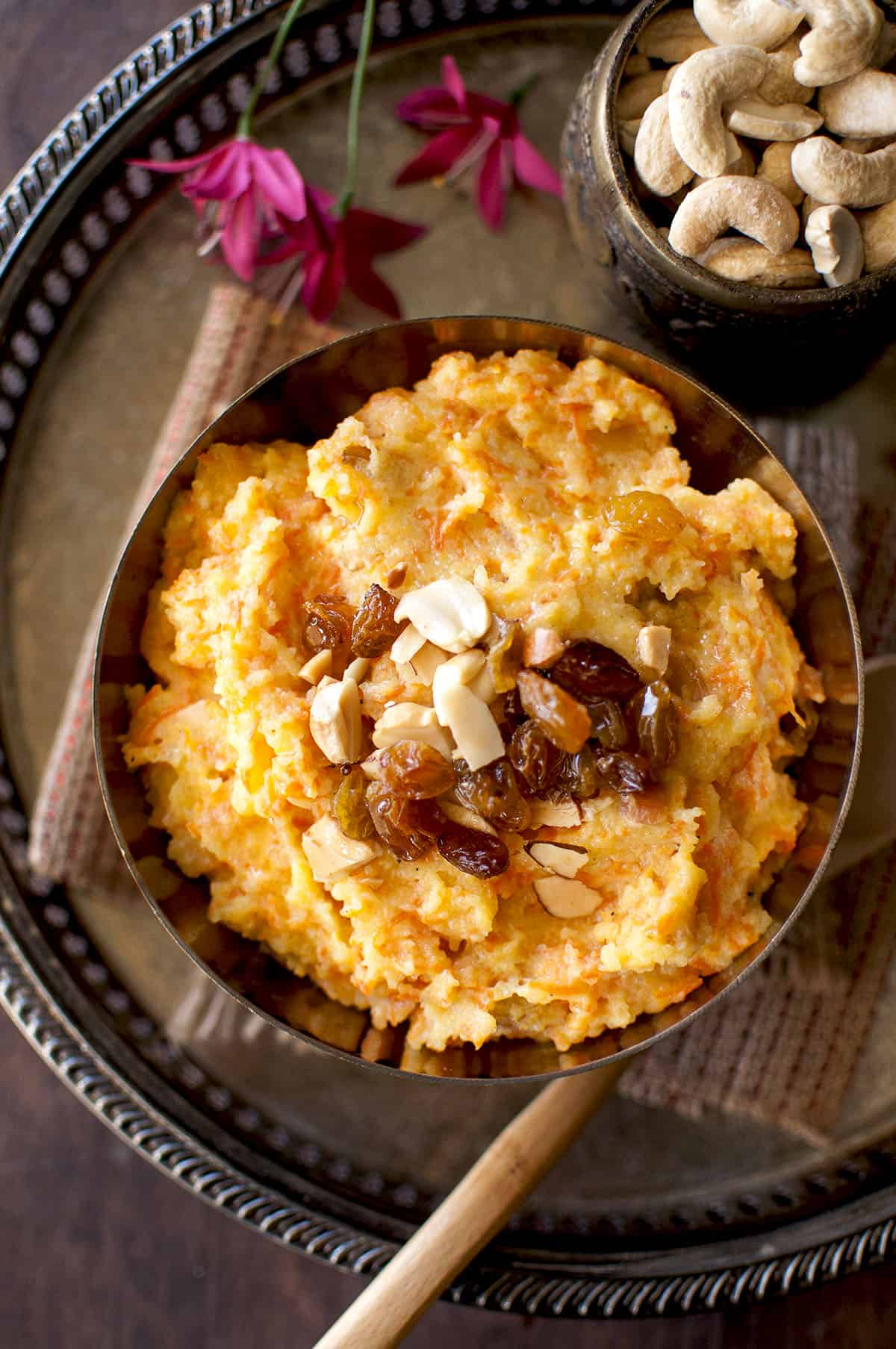 Brass bowl with shahi halwa with carrots topped with raisins and nuts