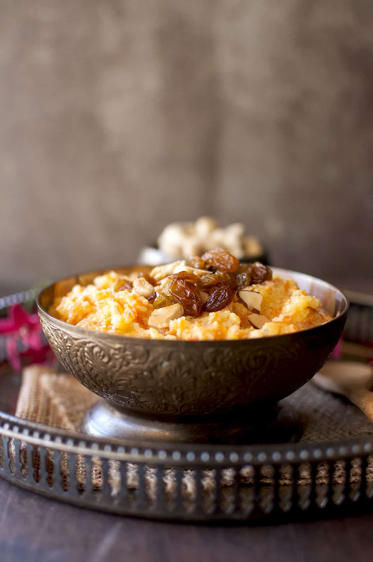 Brass bowl with carrot sooji halwa topped with raisins and cashews