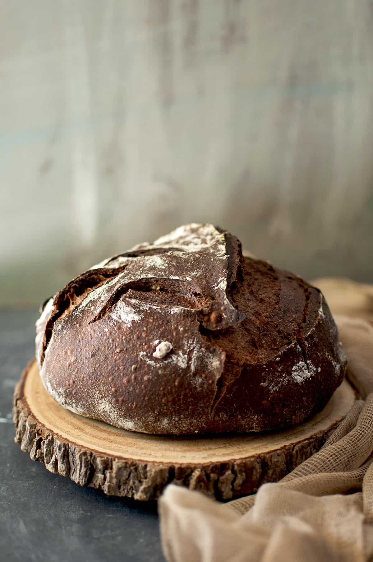 Wooden chopping board with a loaf of chocolate sourdough bread
