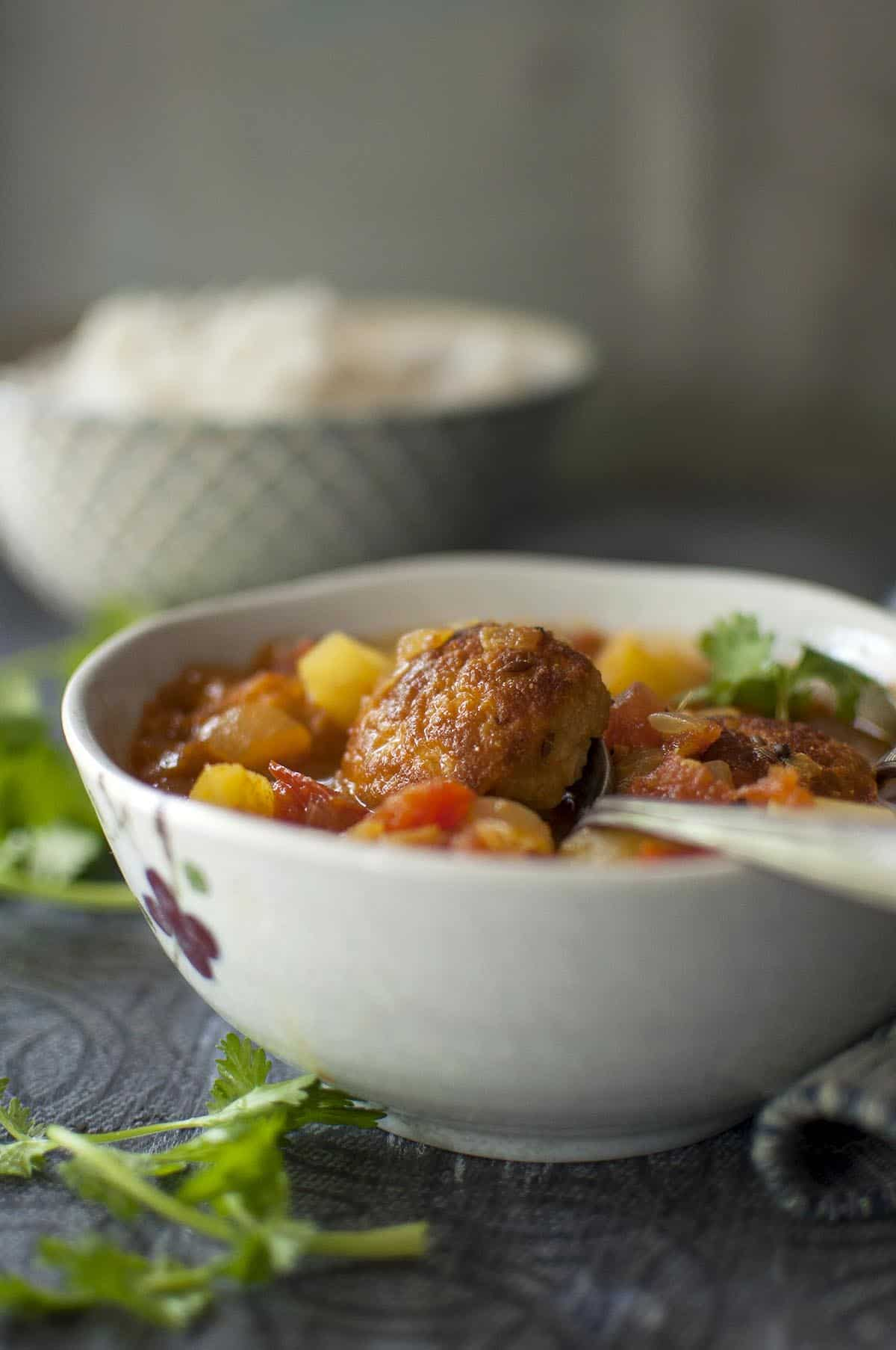 Grey bowl with Bengali fritter curry and a spoon inside