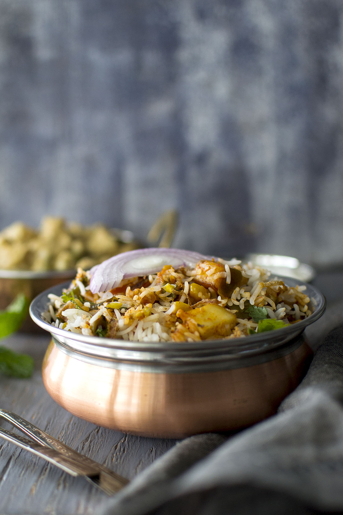 Copper bowl with Vegetable dum biryani topped with sliced red onion