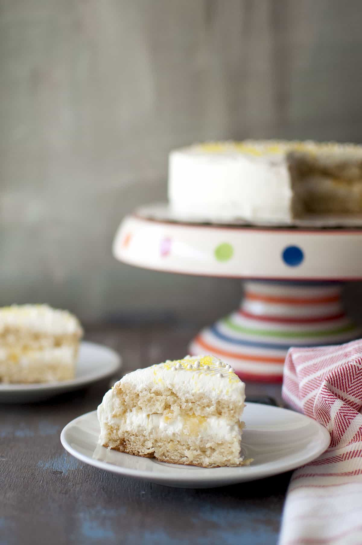 White plate with a slice of moist pineapple cake with a cake stand in the background