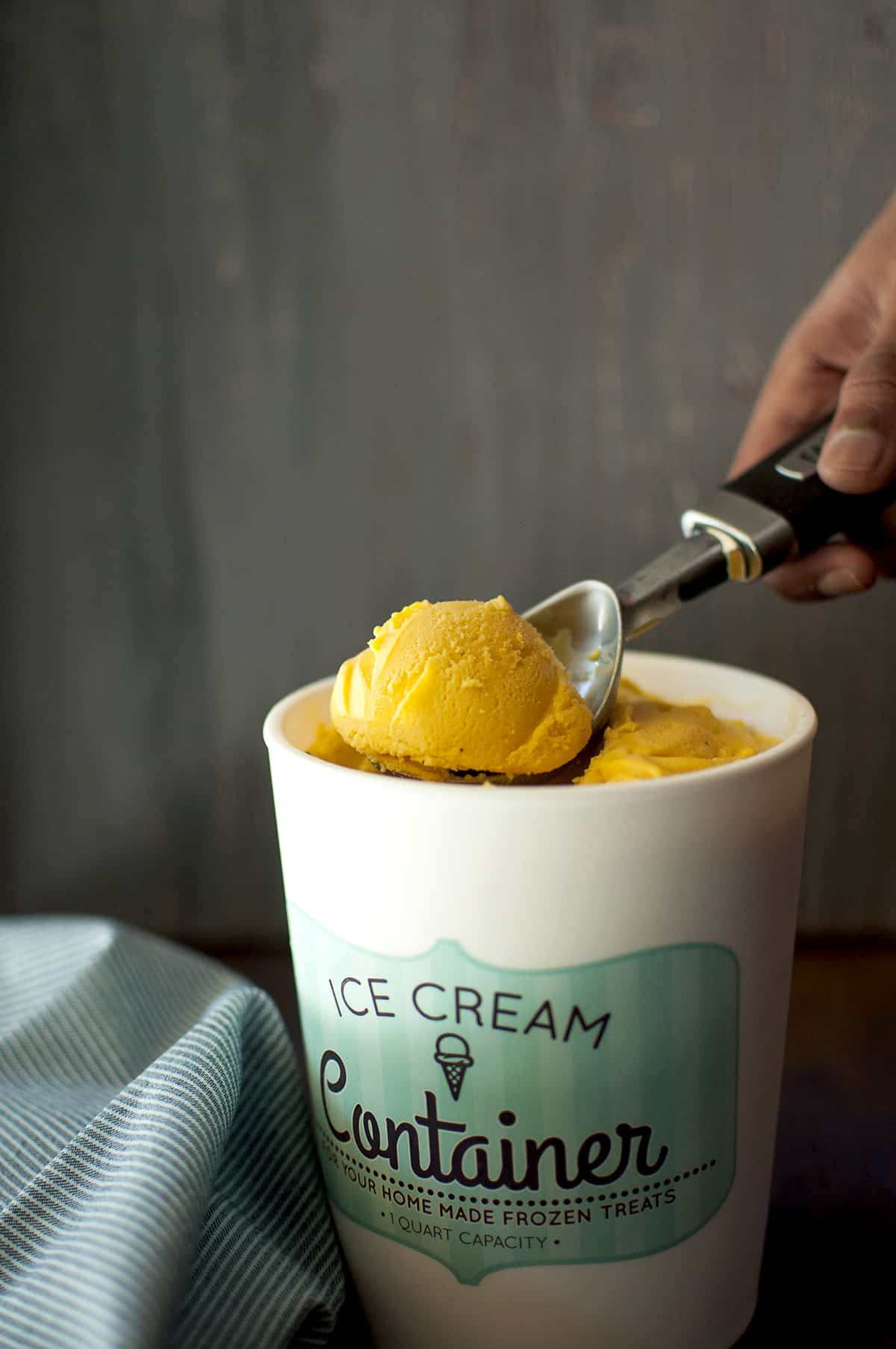 Ice cream container with mango ice cream with a scoop on top