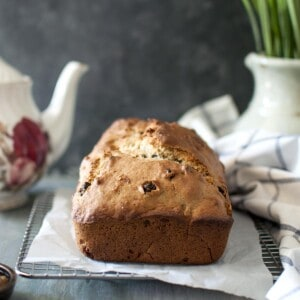 A loaf of banana bread on parchment lined wire rack