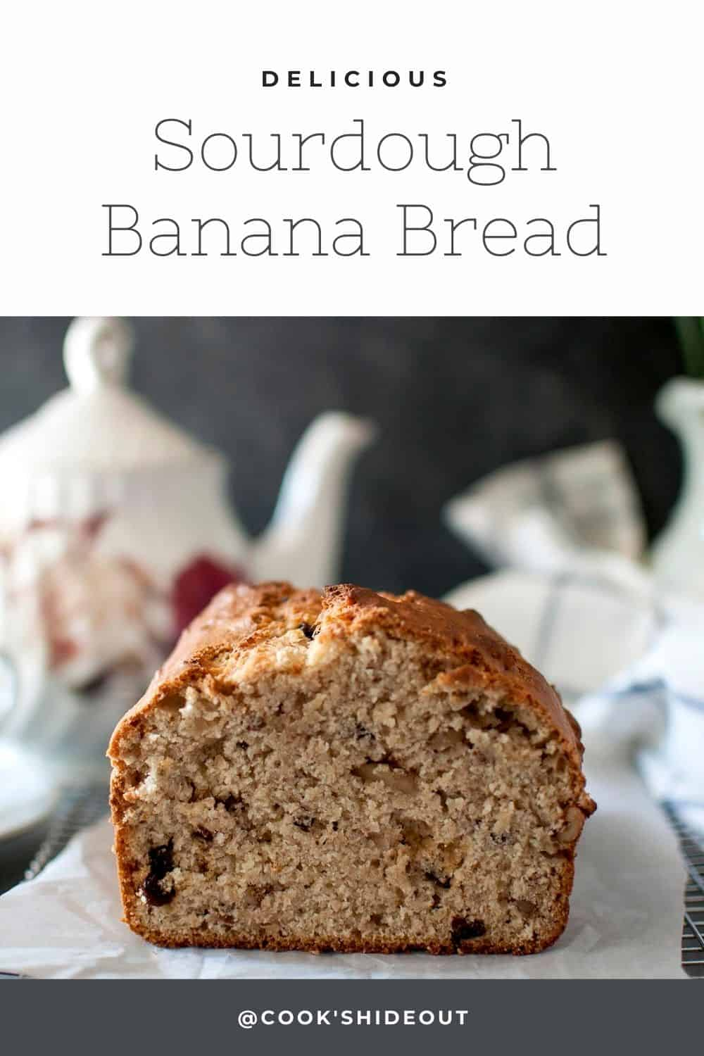 Loaf of banana bread placed on parchment lined wire rack