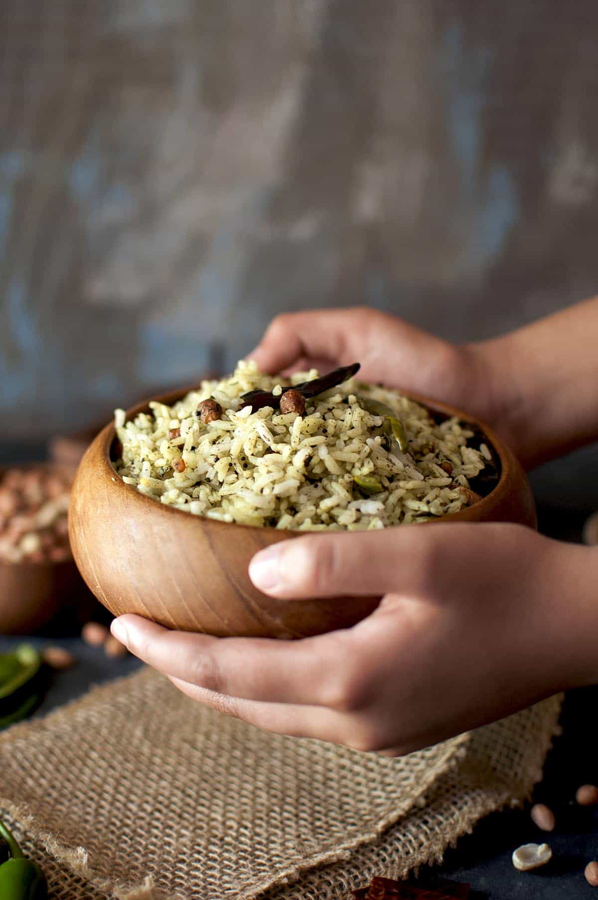Hand holding a wooden bowl with gongura rice