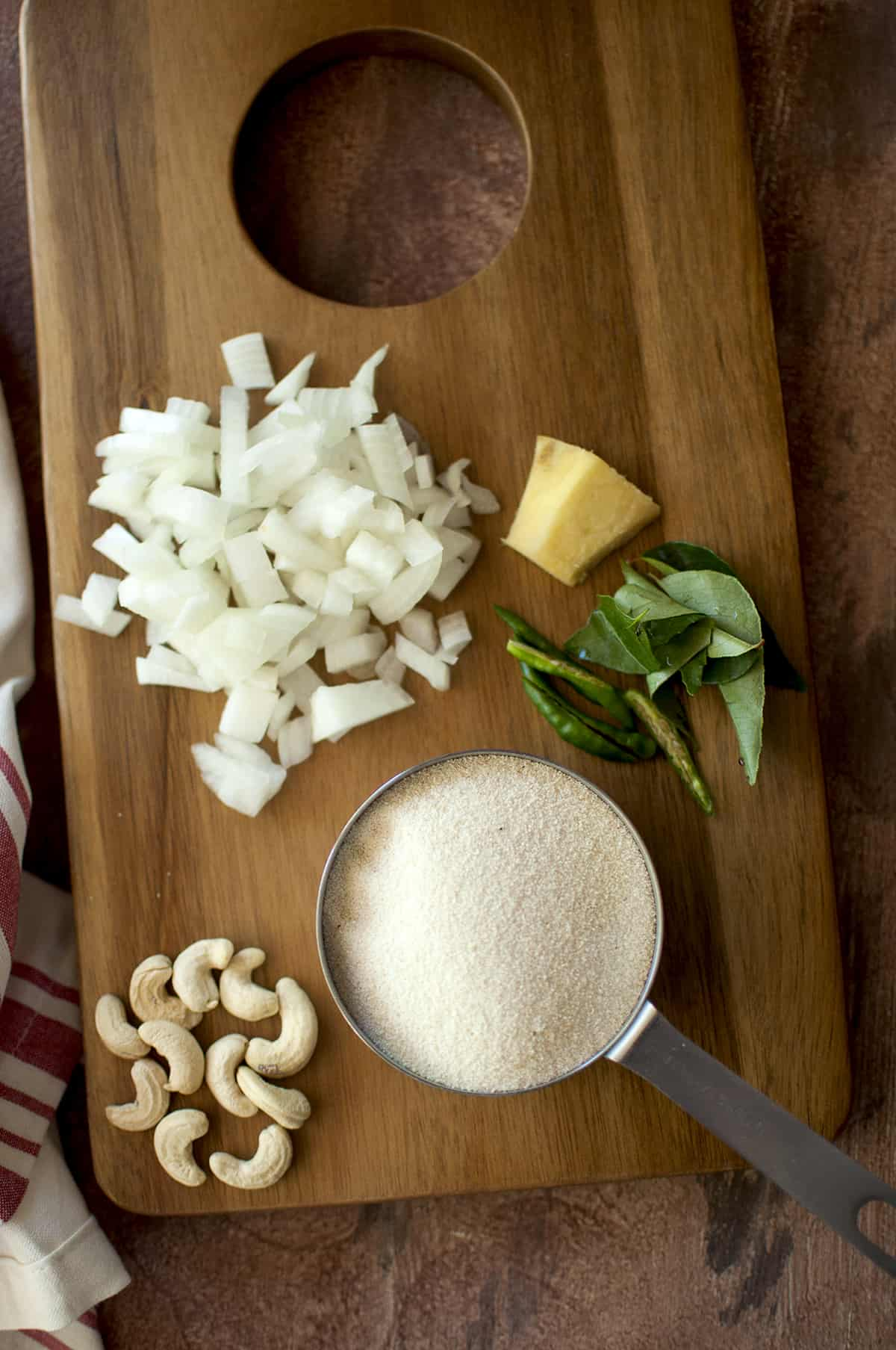 Ingredients for upma on a chopping board - sooji, cashews, chopped onions, ginger, green chilies and curry leaves