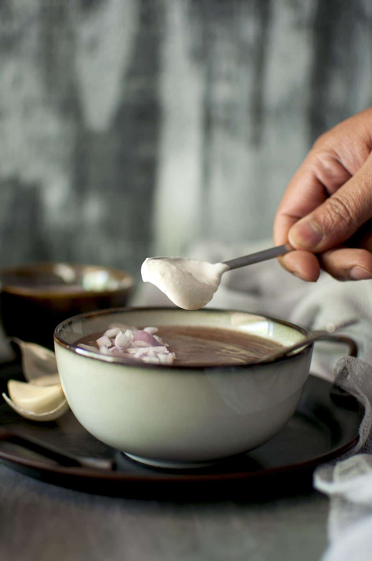 Hand putting a dollop of yogurt into a grey bowl of finger millet soup