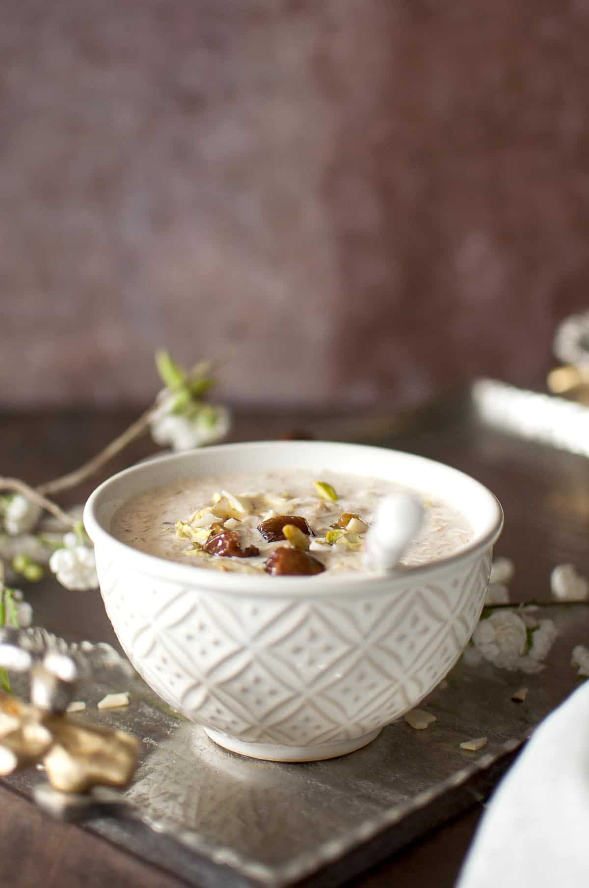White bowl with sheer khurma with a spoon inside