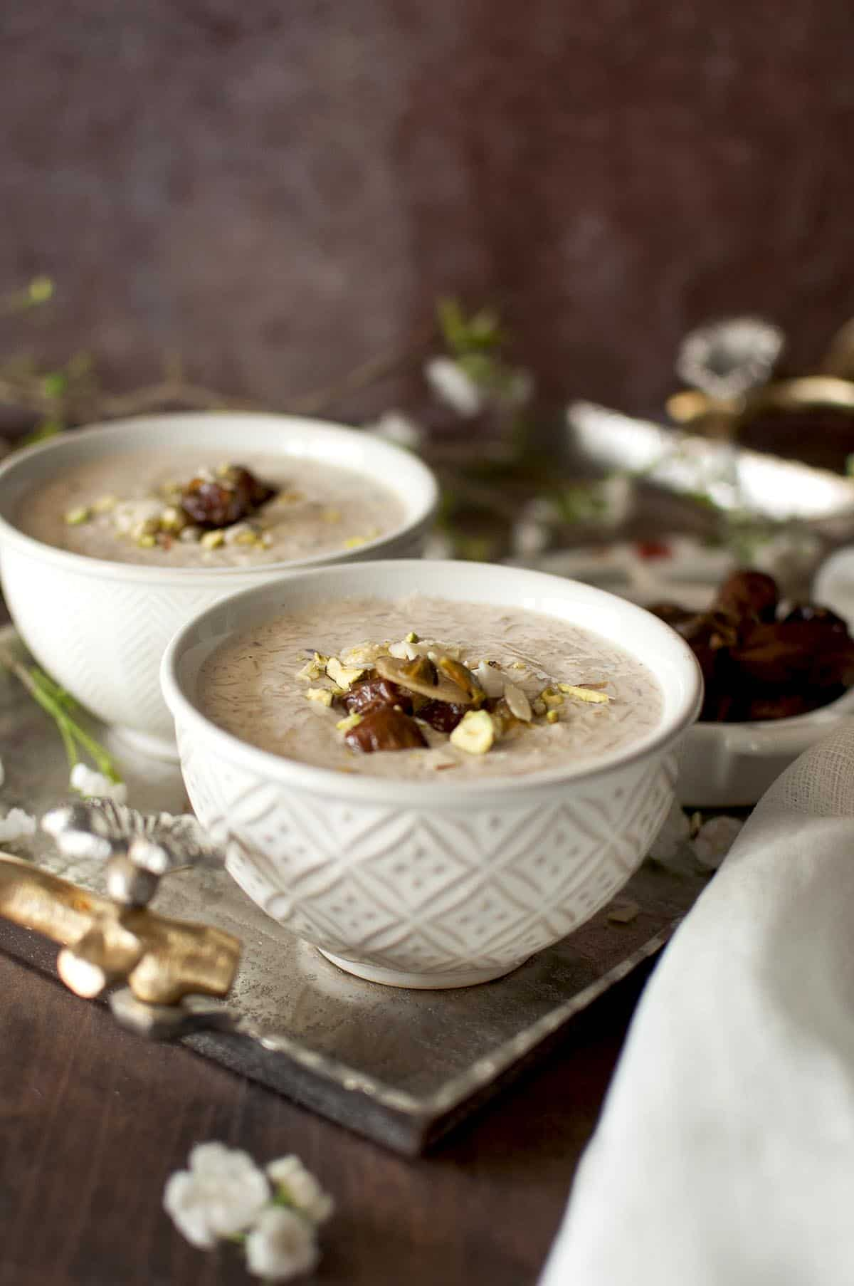 Two cream color bowls with kheer topped with nuts on a silver tray