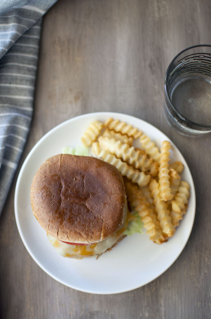 Table with White plate with sandwich, curly fries and glass of water