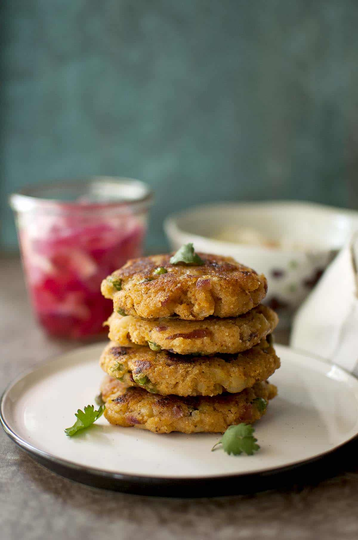 White plate with a stack of round aloo patty