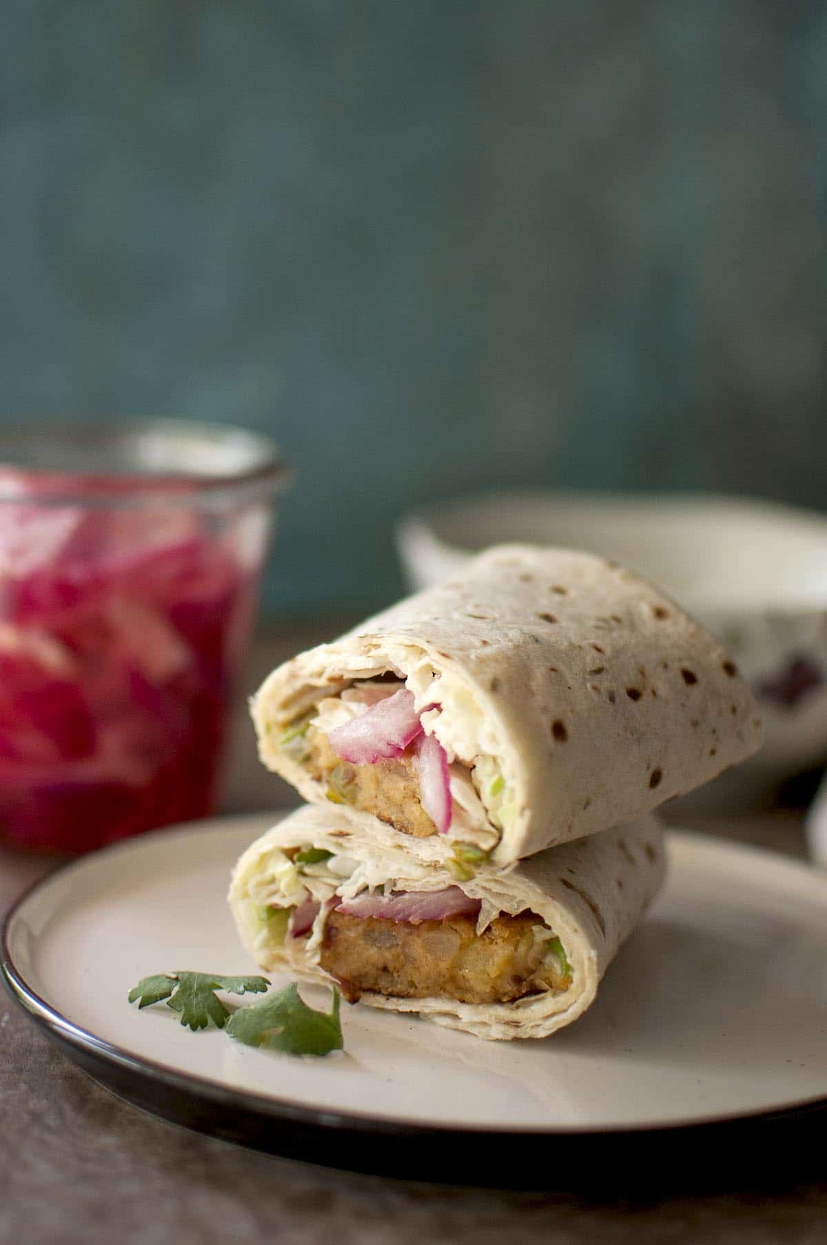 White plate with Aloo tikki wrap halves stacked on top of each other