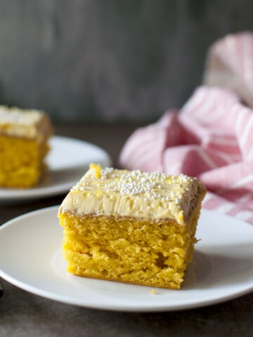White plate with a square slice of frosted mango cake