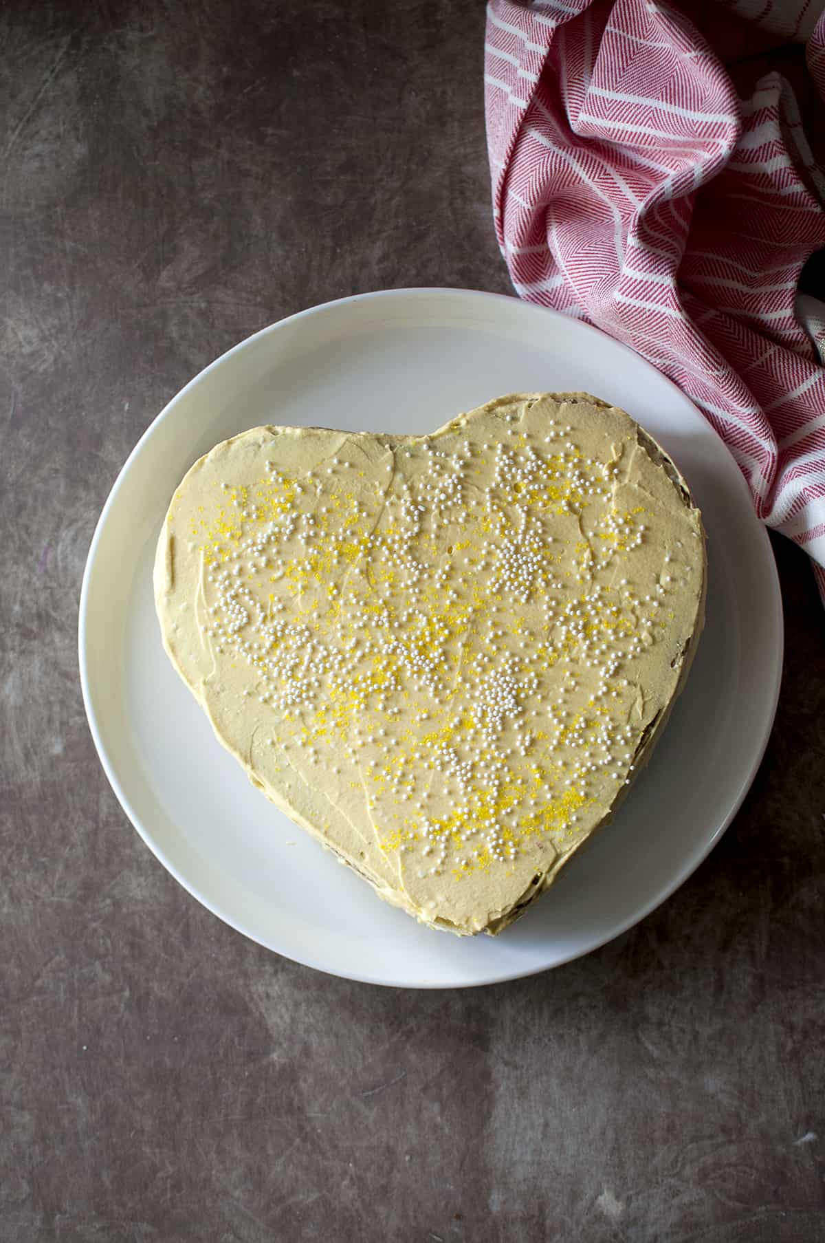 White plate with a heart shaped mango cake with yellow frosting and sprinkles