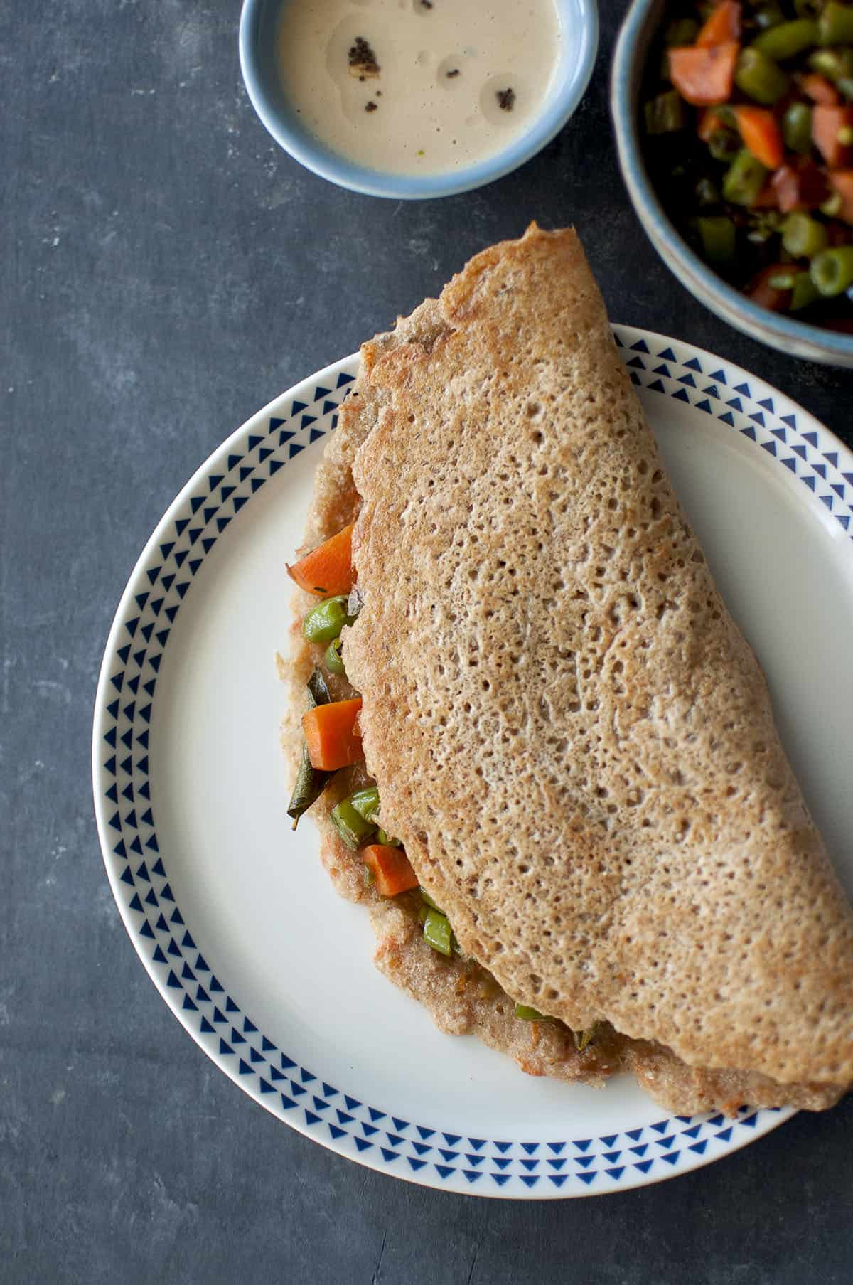 White plate with instant wheat dosa stuffed with carrot & green bean saute