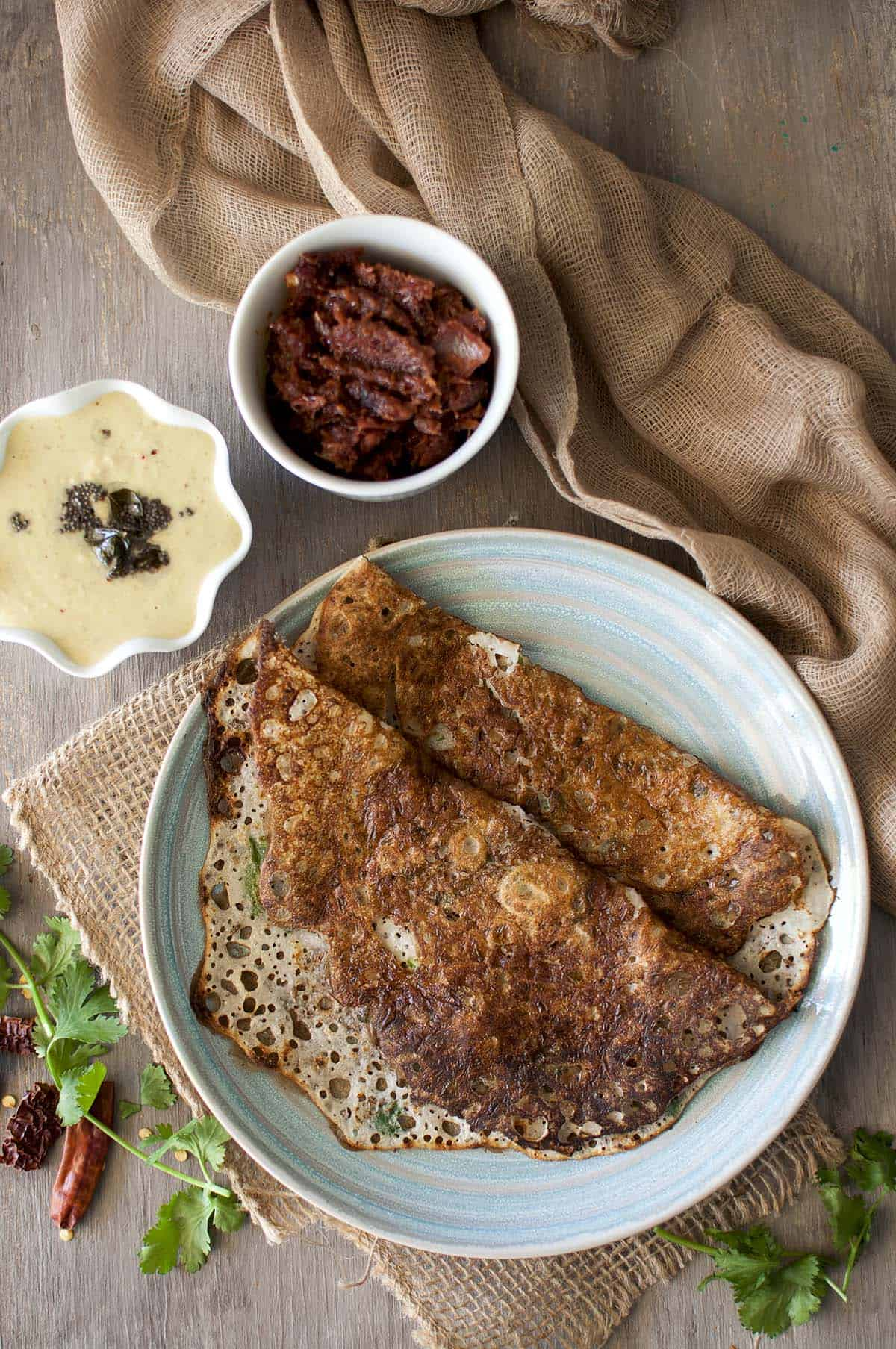 Blue plate with rava dosa with bowls of onion chutney and peanut chutney