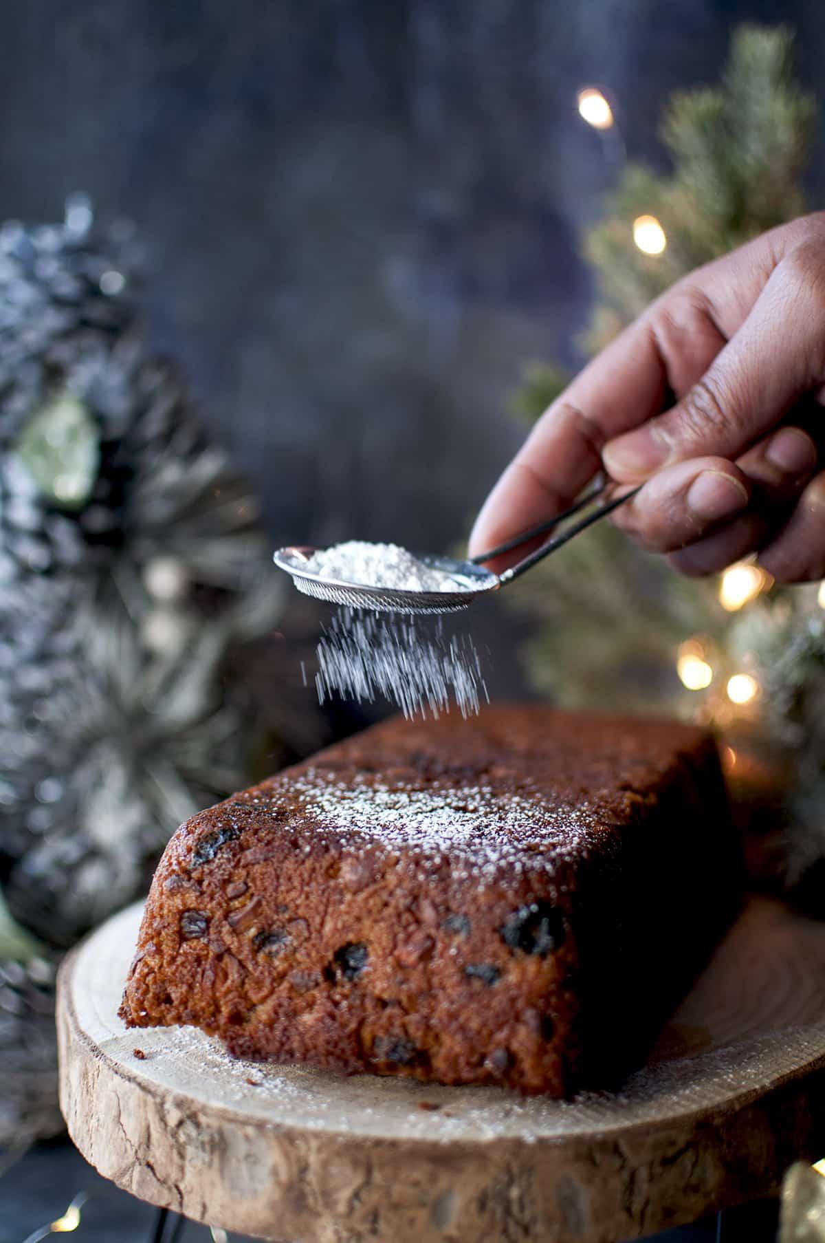 Hand sprinkling powdered sugar on eggless plum cake