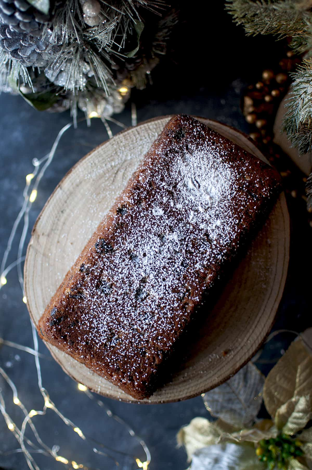 Loaf of plum cake sprinkled with powdered sugar on a wooden stand