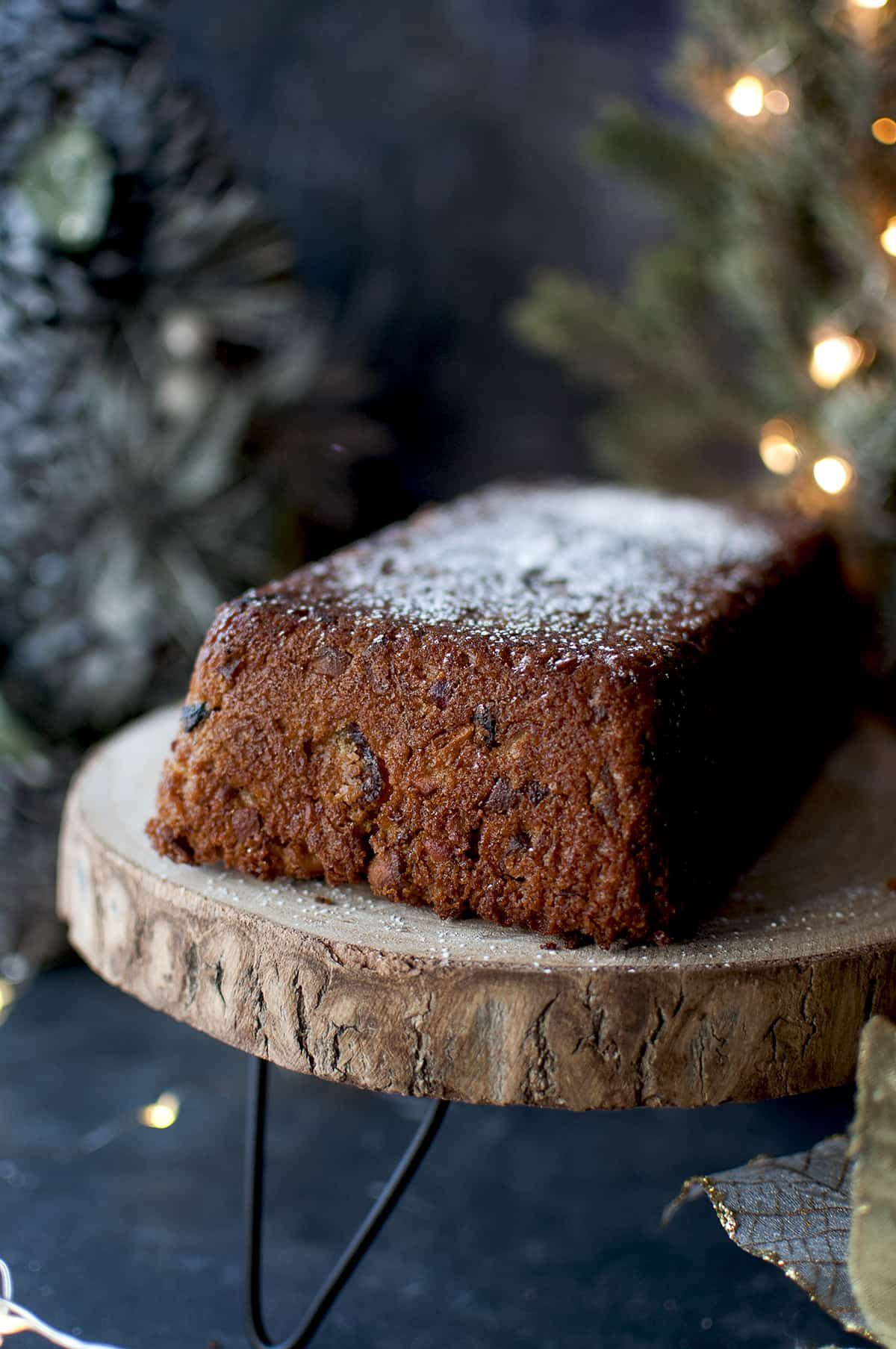 Vegan Fruit cake sprinkled with powdered sugar on a wooden stand