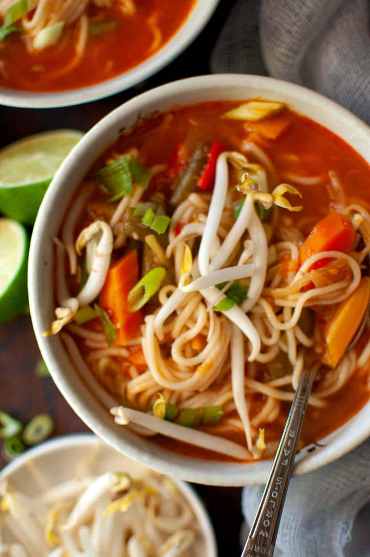White bowl with veg noodle soup topped with bean sprouts