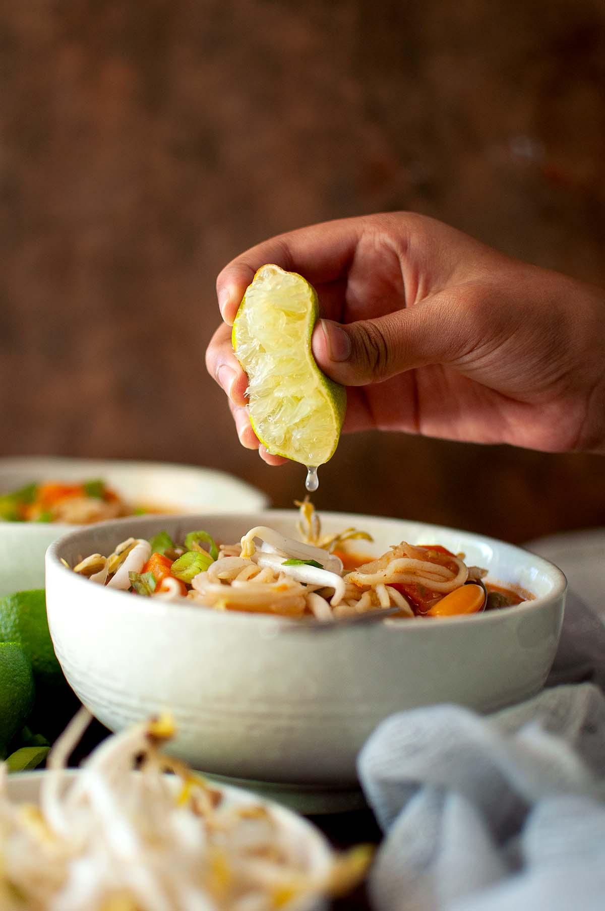 Hand drizzling lemon juice onto a bowl of noodle soup