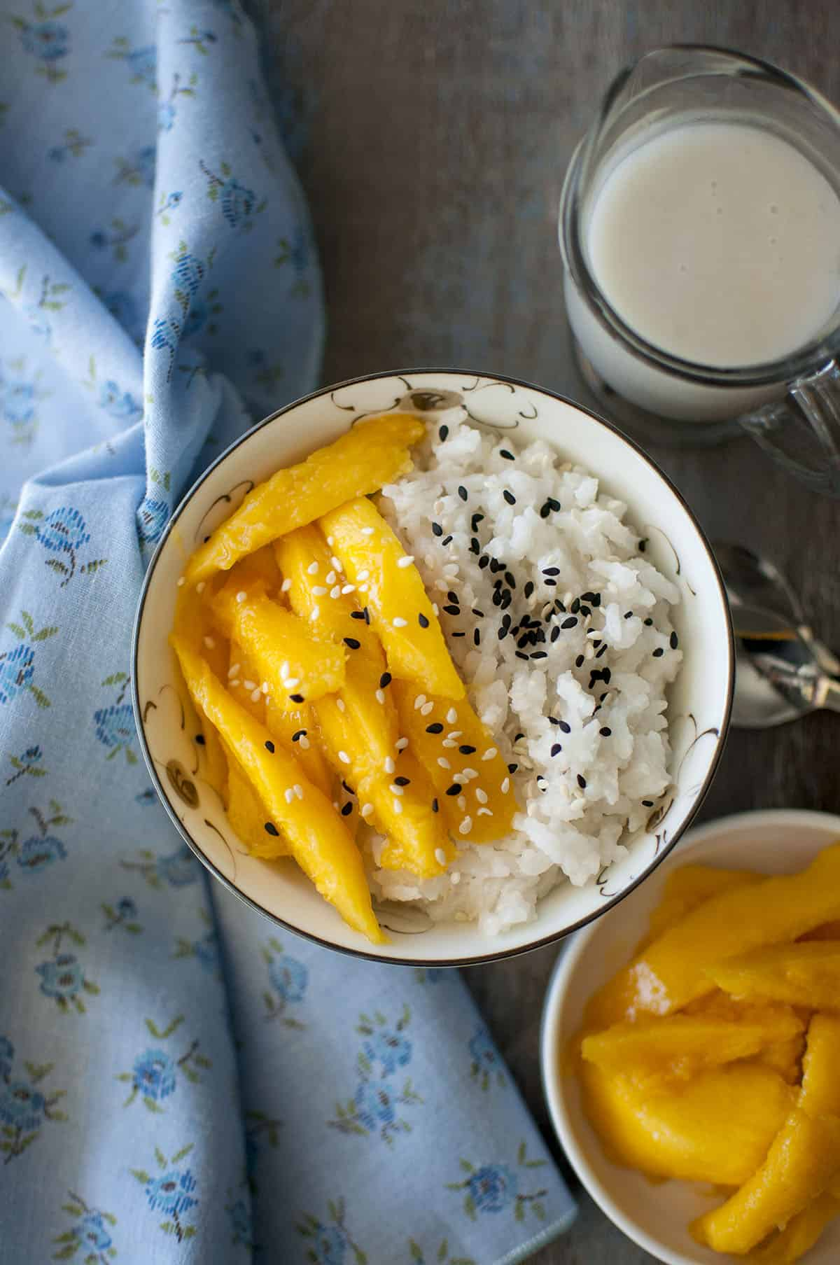 White Bowl with sticky rice and chopped mangoes topped with sesame seeds