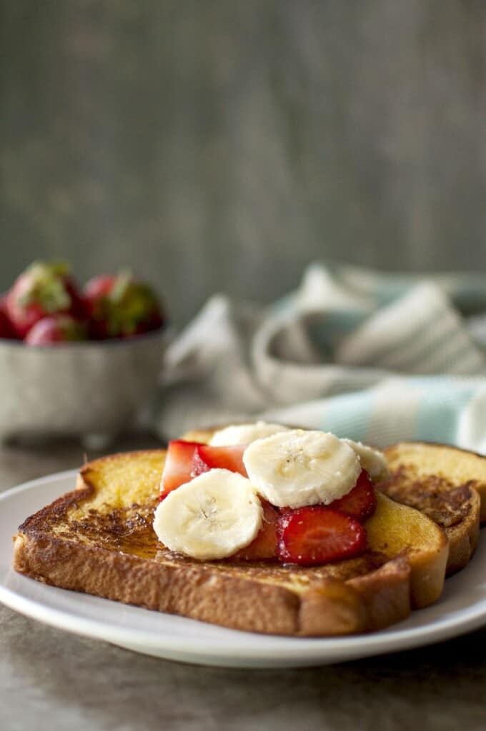 white plate with French toast topped with chopped fruit