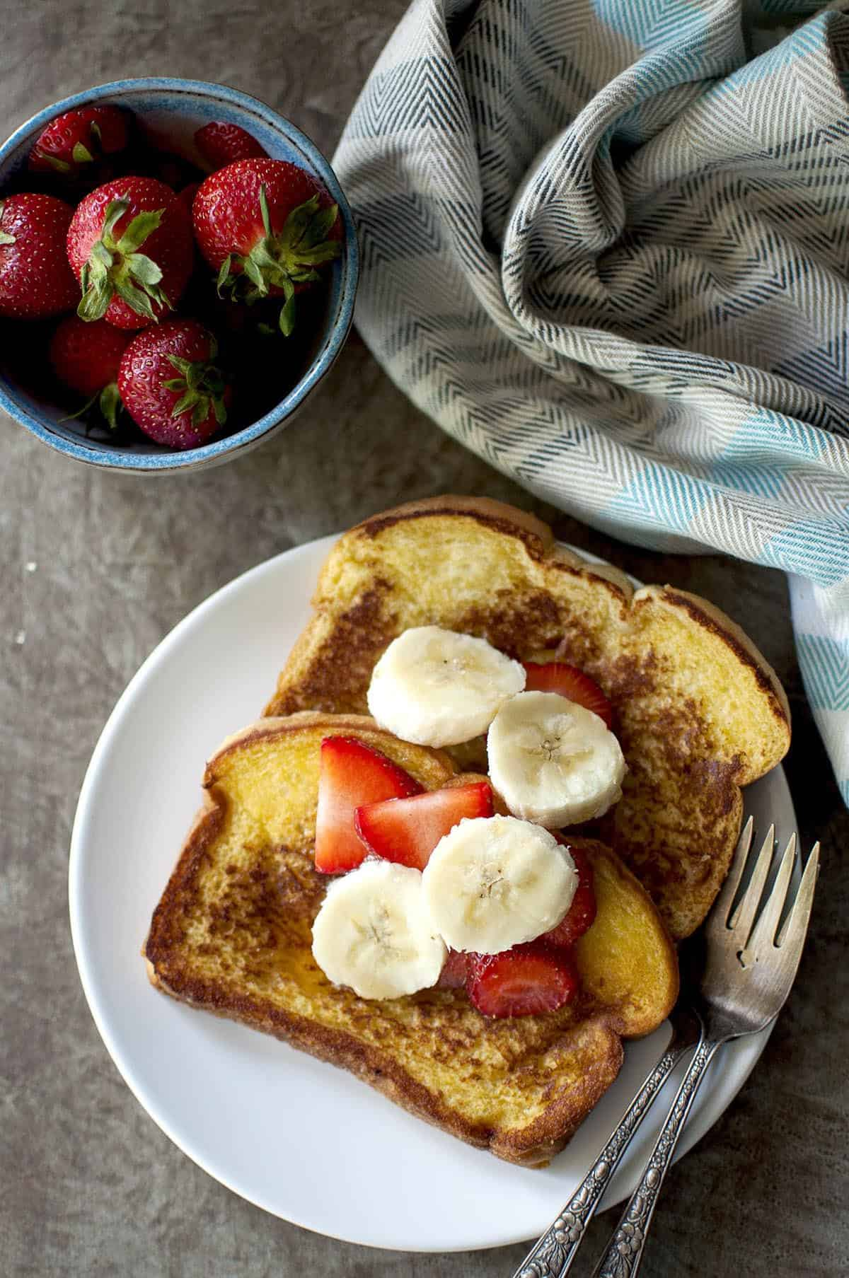 White plate with 2 french toast slices topped with fresh fruit
