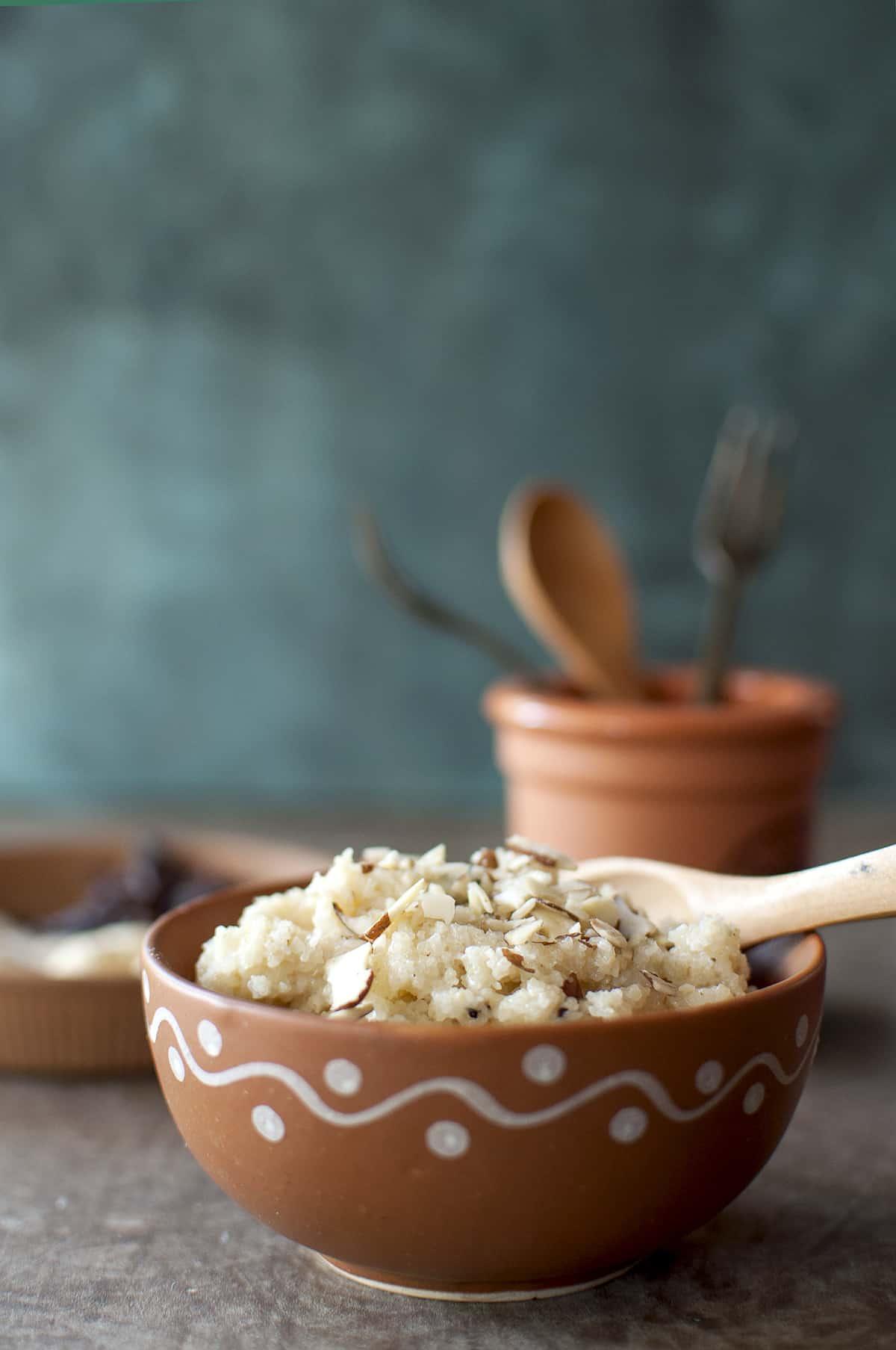 Terracotta bowl with rava kesari topped with almond flakes