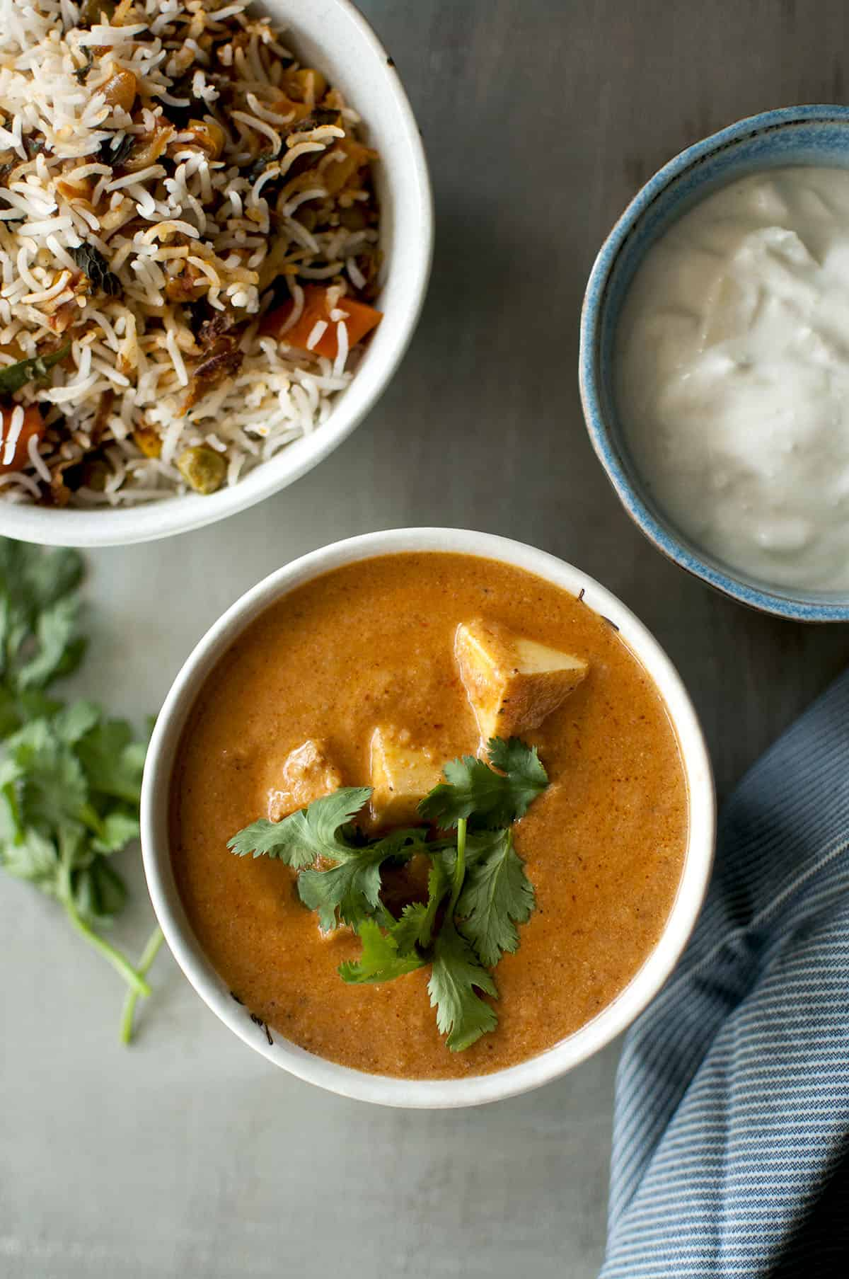 White bowl with paneer tikka masala with a rice pilaf and yogurt in the background