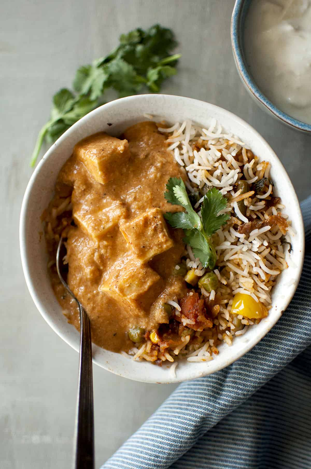 White bowl with rice pilaf and paneer curry