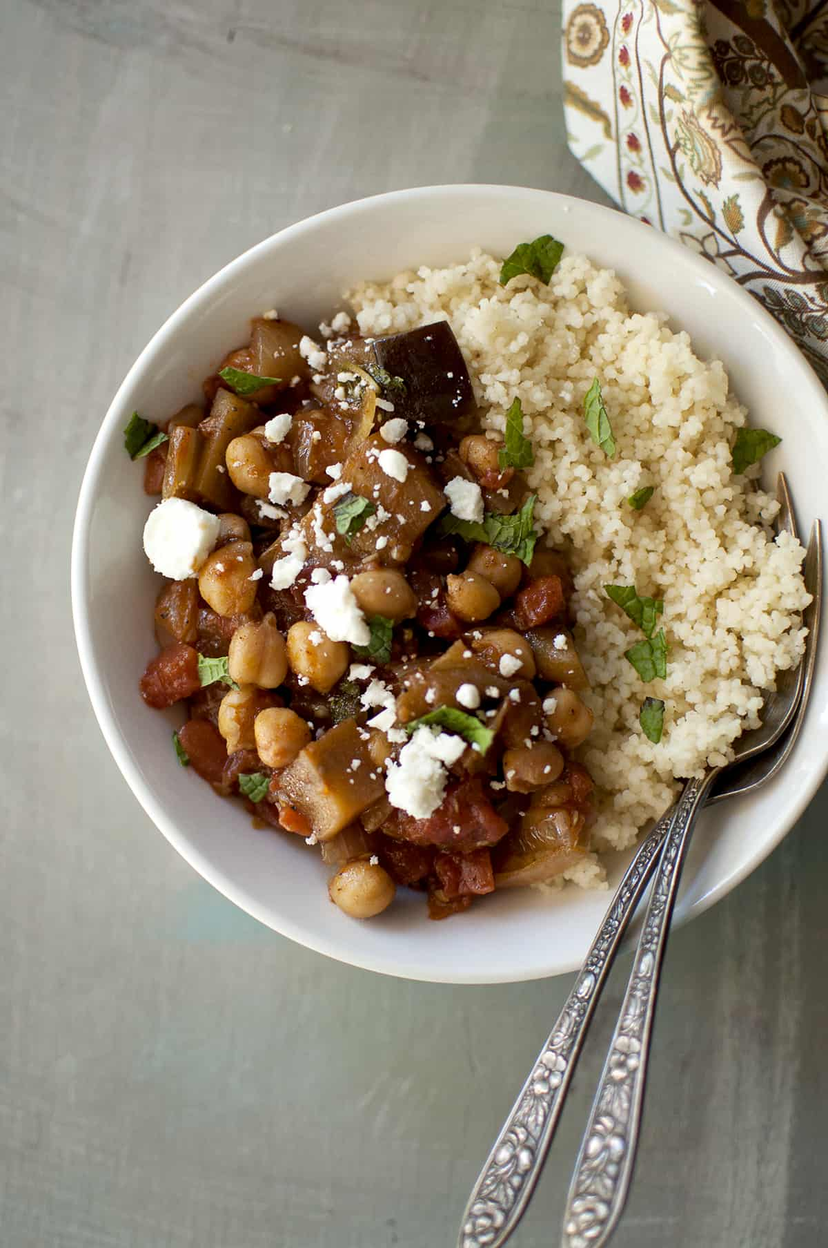 White bowl with eggplant and chickpea stew served with couscous