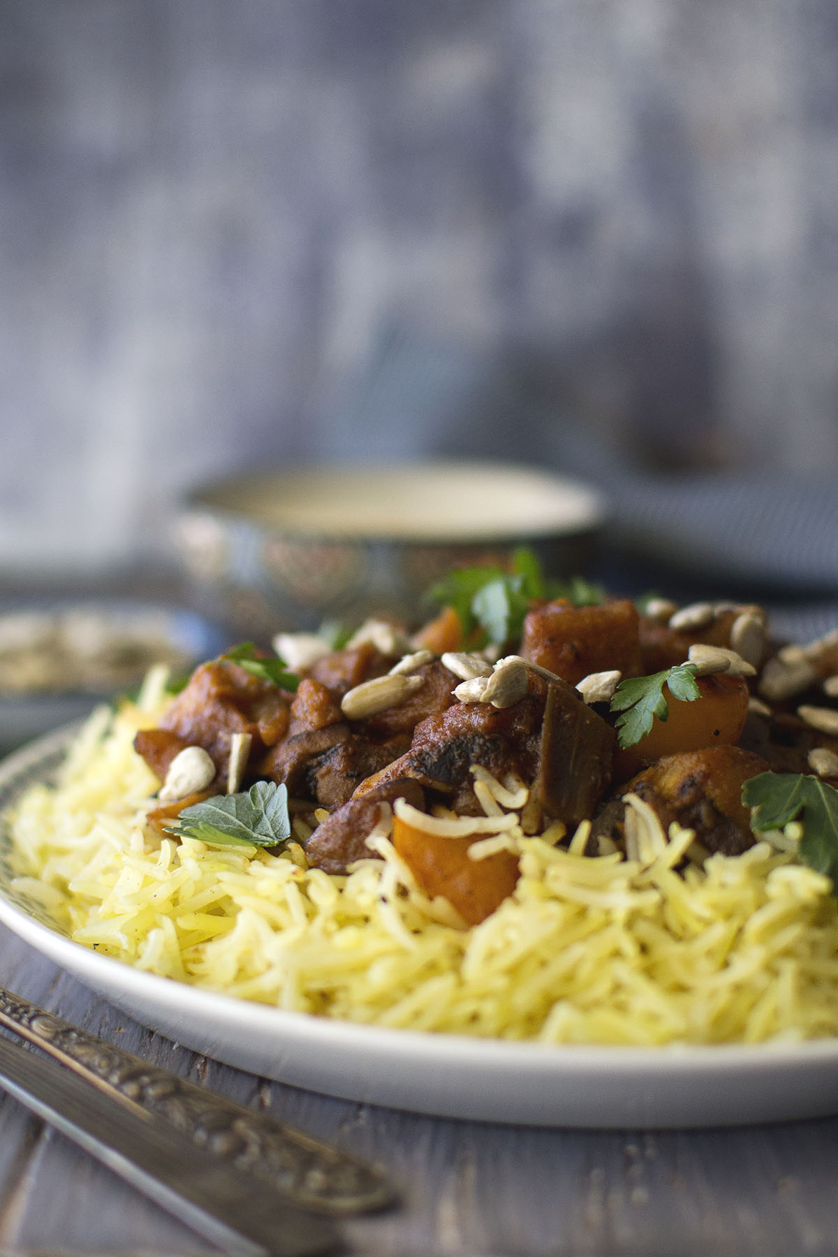 White plate with yellow rice, vegetables, sunflower seeds and parsley
