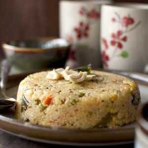 Brown plate with jowar upma topped with cashews