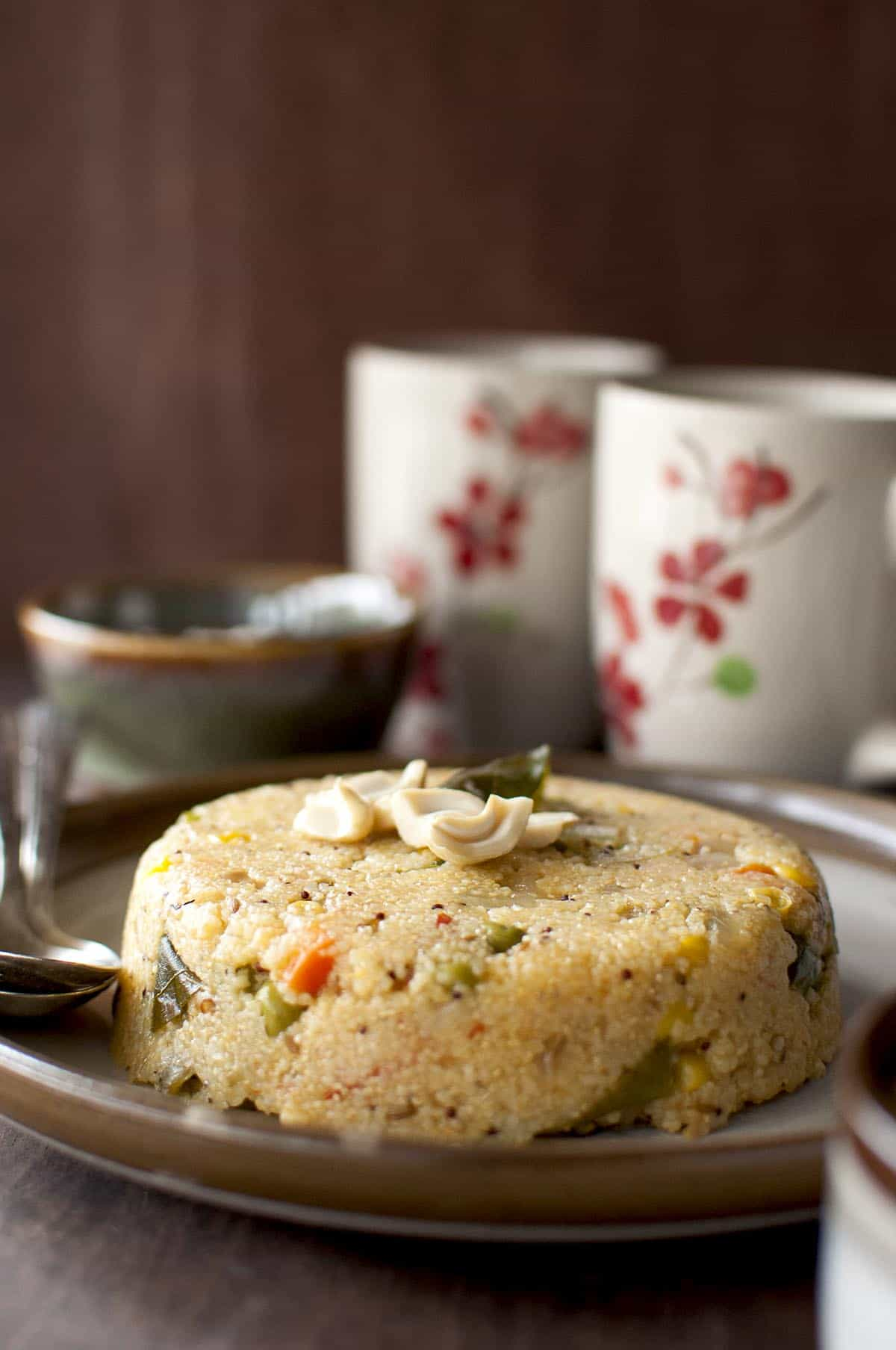 brown plate with jonna rava upma topped with cashews and curry leaves and 2 coffee mugs in the background