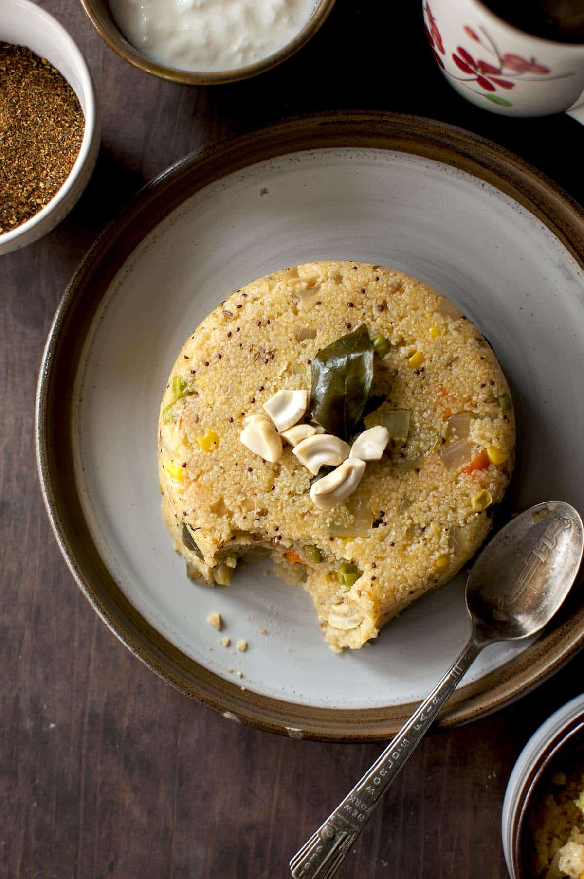 Grey plate with savory millet porridge and a spoon