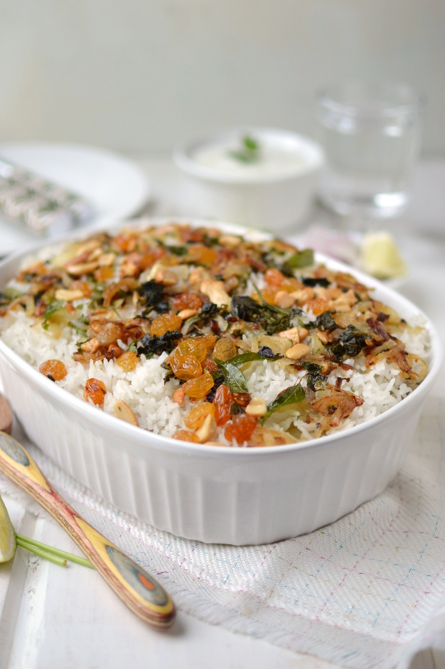White baking pan with rice topped with nuts, raisins and herbs