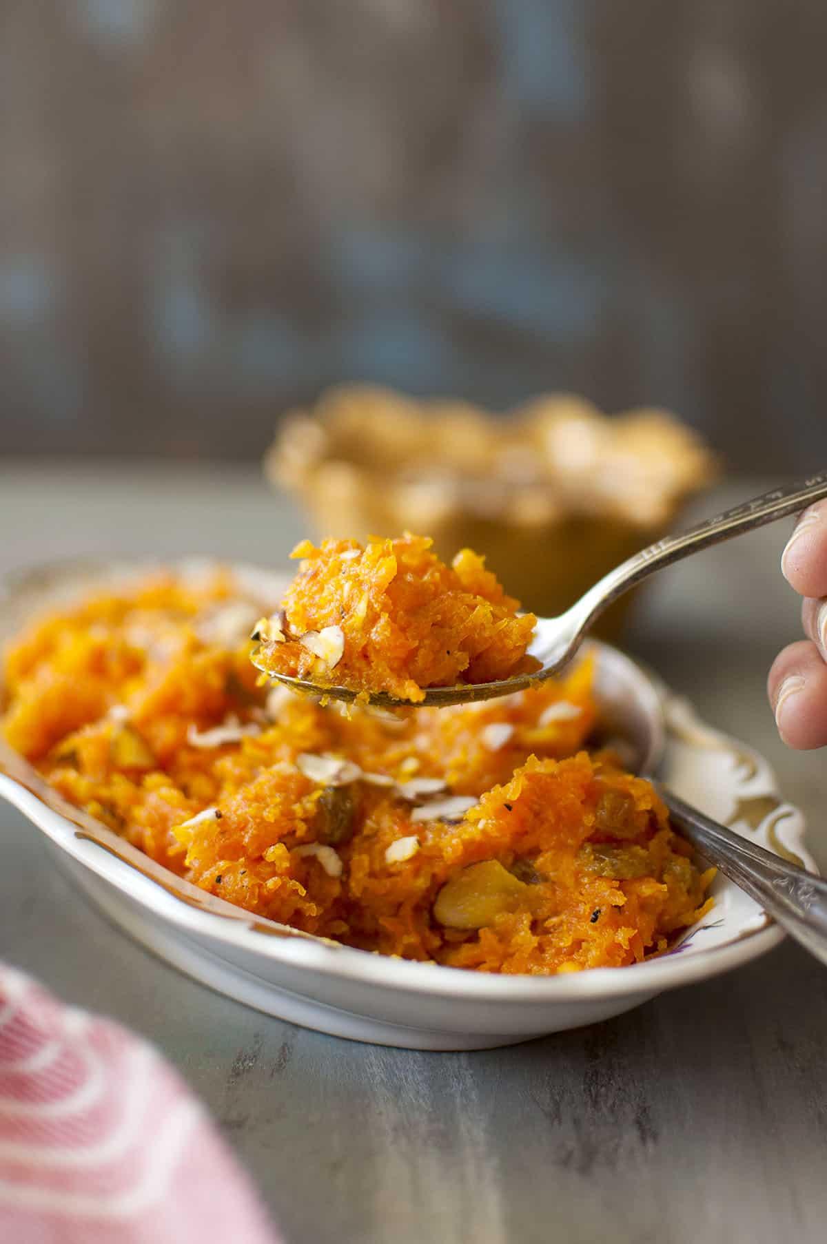 hand holding spoon with carrot halva